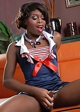 Sexy ebony shemale Bambie strips naked on an orange sofa and proceeds to pleasure her thick dick